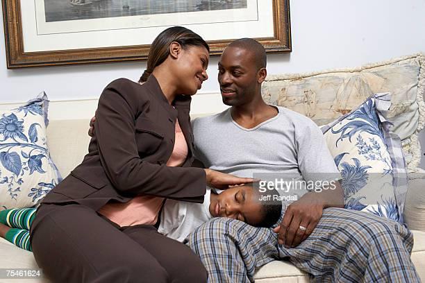 Couple sitting on sofa, boy (6-7) sleeping on father's lap