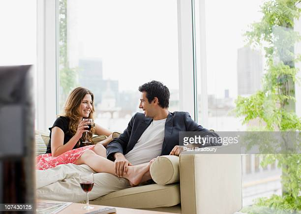 couple sitting on sofa drinking red wine - women of penthouse stock photos and pictures