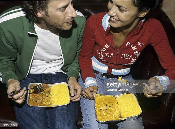 couple (30-35 years) sitting on sofa eating take-away food from alluminium tray on their laps - 25 29 years stock pictures, royalty-free photos & images