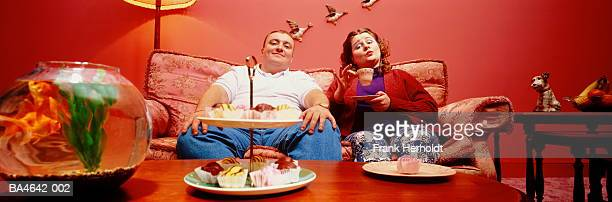 couple sitting on sofa, having tea and cakes - funny fat women stock pictures, royalty-free photos & images