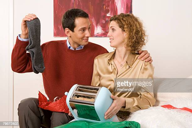 'Couple sitting on sofa, holding toaster and socks'