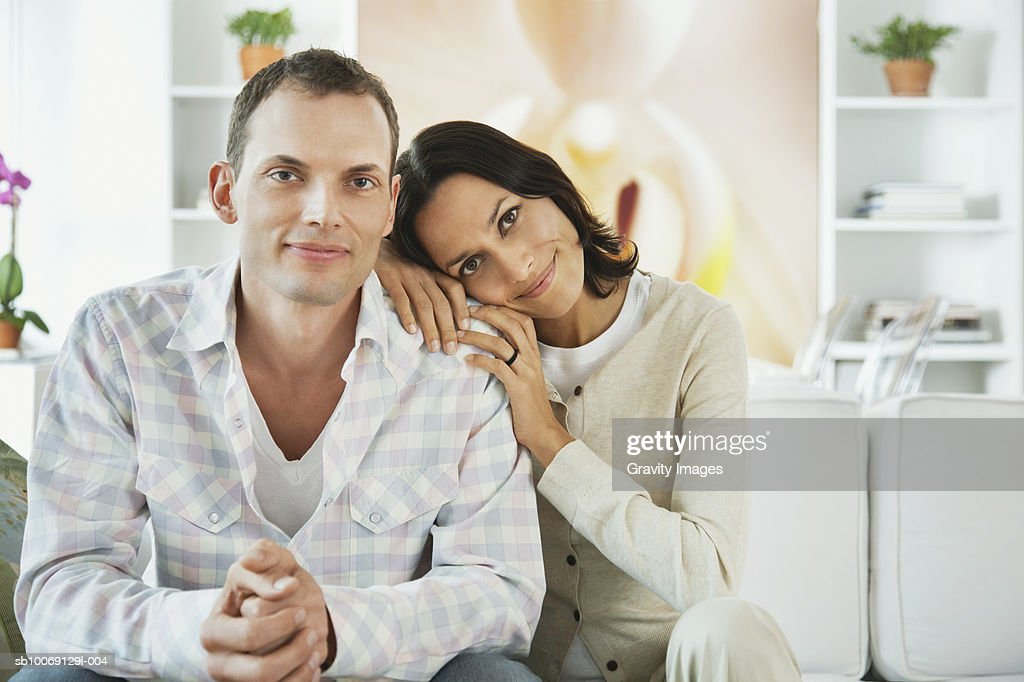 Couple sitting on sofa in living room, smiling, portrait : Stockfoto