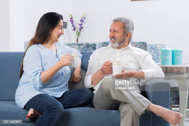 couple sitting on sofa in living room stock photo - husband stock pictures, royalty-free photos & images