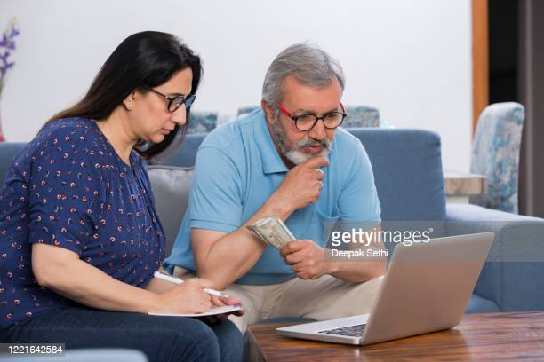 couple sitting on sofa in living room stock photo - bonding stock pictures, royalty-free photos & images