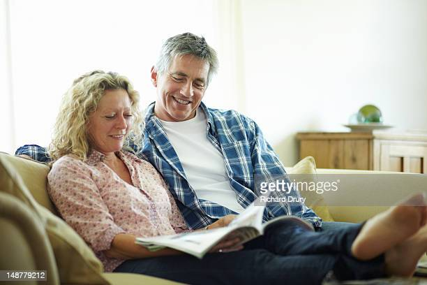couple sitting on sofa looking at magazine - magazine stock pictures, royalty-free photos & images