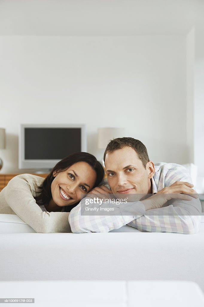Couple sitting on sofa, smiling, portrait : Stockfoto