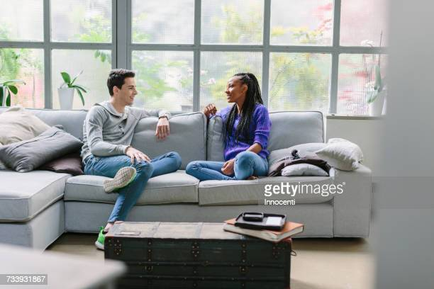 couple sitting on sofa talking - florence douillet photos et images de collection