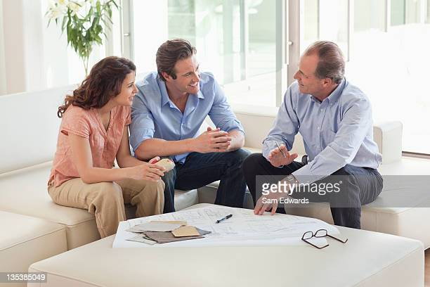 couple sitting on sofa talking to financial advisor - building contractor stock pictures, royalty-free photos & images
