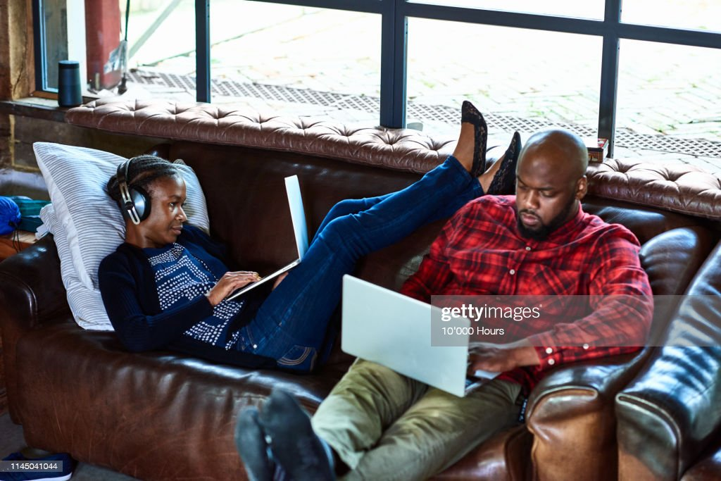Couple sitting on sofa using laptops and relaxing : Stock Photo