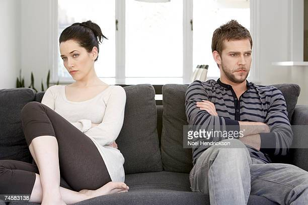 couple sitting on sofa with arms folded, looking angry - novio relación humana fotografías e imágenes de stock