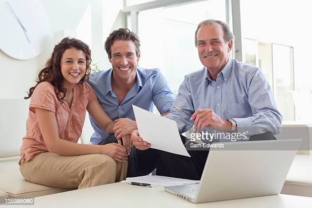 Couple sitting on sofa with financial advisor