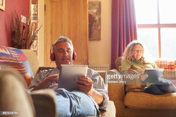 Couple sitting on sofas using digital tablets