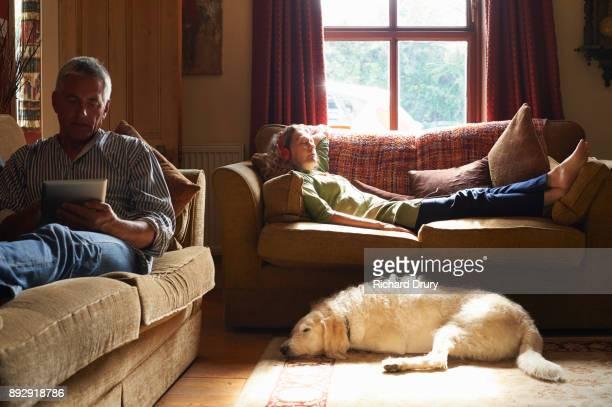 Couple sitting on sofas using digital tablets