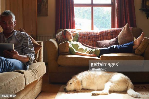 couple sitting on sofas using digital tablets - convenience stock pictures, royalty-free photos & images