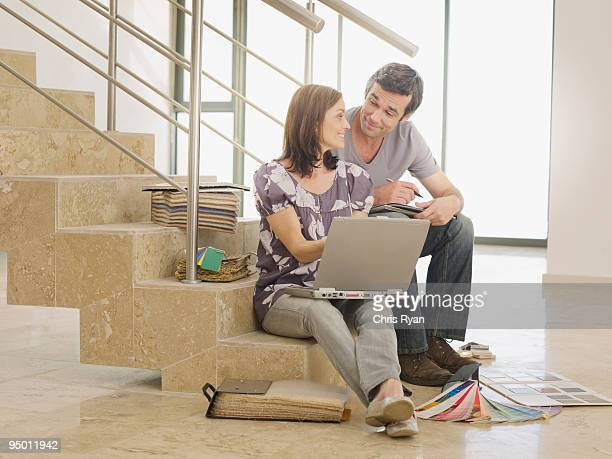 Couple sitting on staircase with laptop and paint samples