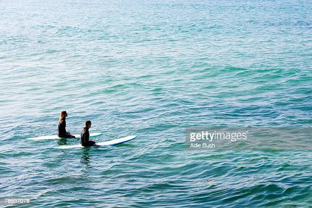 Couple sitting on surfboards in the water.