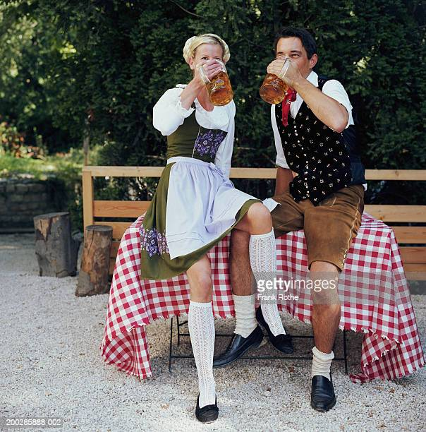 couple sitting on table drinking beer steins outdoors - bavaria stock pictures, royalty-free photos & images