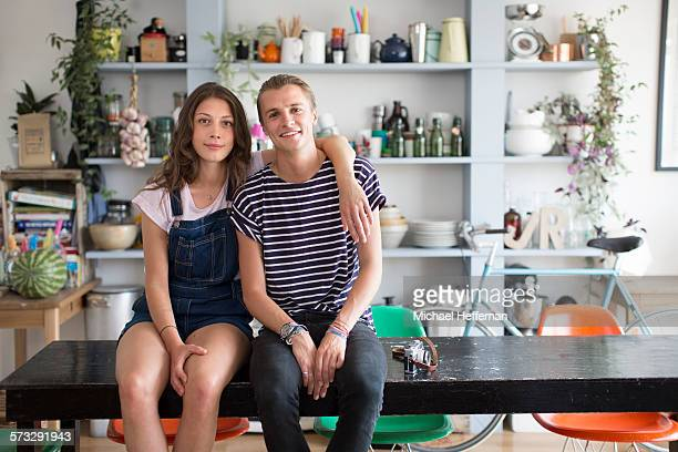 couple sitting on table in their apartment - young couple stock pictures, royalty-free photos & images