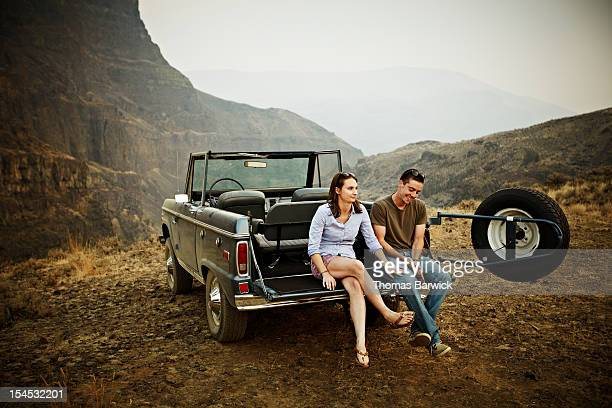 Couple sitting on tailgate of convertible