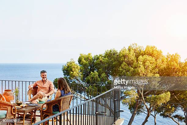 Couple sitting on terrace surrounded by ocean