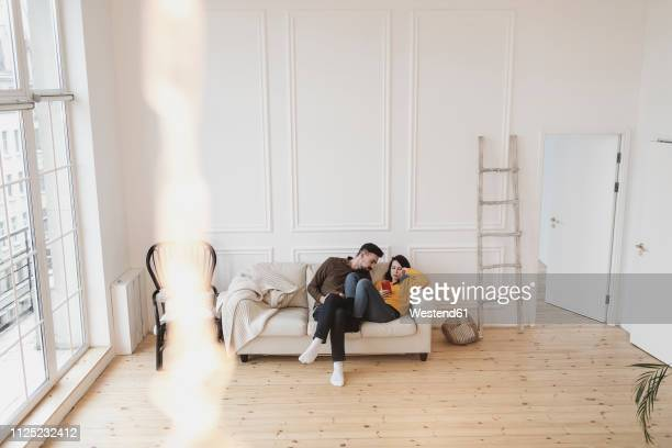 couple sitting on the couch in the living room of new home looking at cell phone - couples nus photos et images de collection
