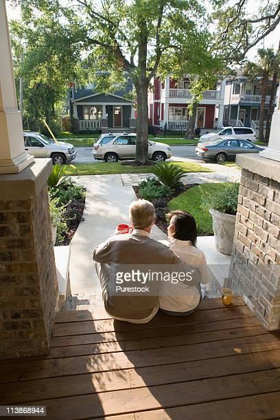 Couple sitting on the front steps of their house