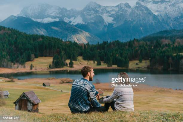 Couple sitting on the meadow near  Gerold lake in Alps