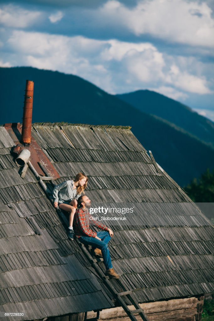 Couple sitting on the roof of wooden house in mountains : Stock Photo