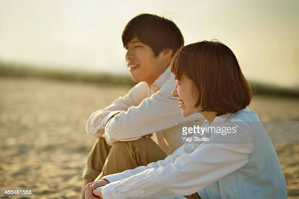 Couple sitting on the sand on the beach