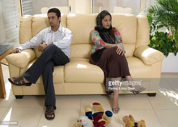 Couple sitting on the sofa in the living room angry with each other