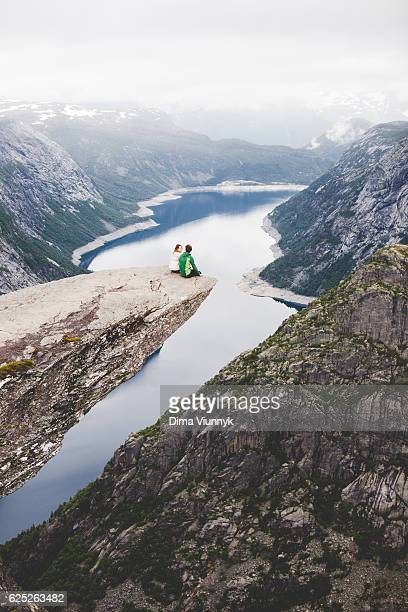Couple sitting on the Trolltunga in Norway