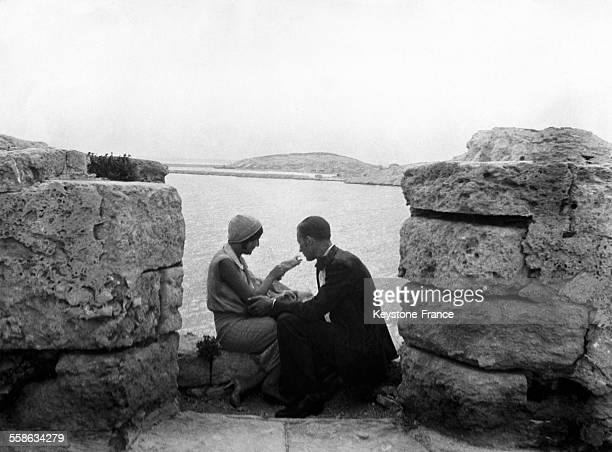 Couple sitting on the Wall of the Chateau d'If, in Frioul Archipelago, France, in 1920.