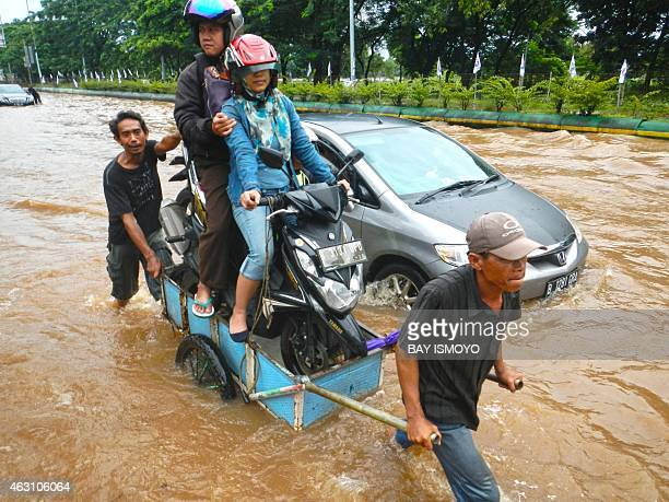Couple sitting on their motorcycle cross a flooded road on a cart in Jakarta on February 10, 2015. Heavy monsoon rains have flooded many sections of...