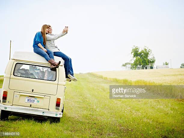 Couple sitting on top of van taking photo