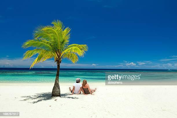 Paar sitzt am tropischen Strand