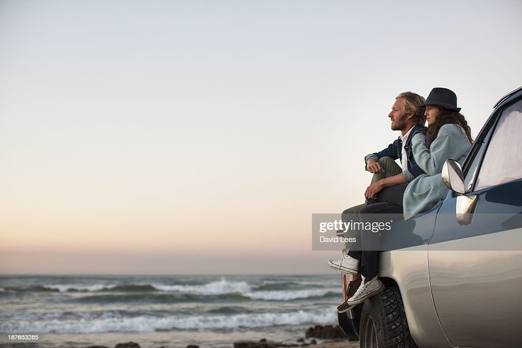 Couple sitting on truck looking at ocean view : Stock Photo