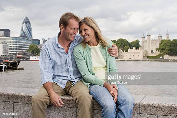Couple sitting on wall by River Thames