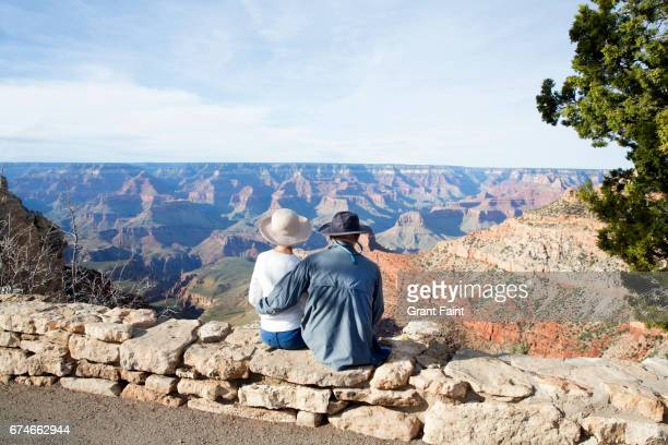 couple sitting on wall, overlooking view near entrance grand canyon - canyon stock pictures, royalty-free photos & images