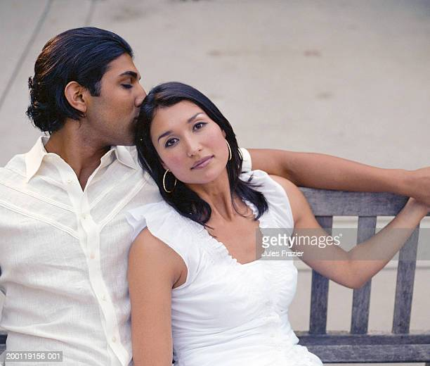 Couple sitting on wood bench, man kissing woman's head