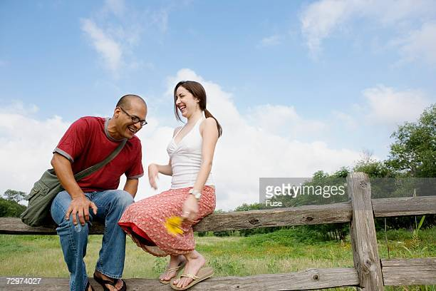 Couple sitting on wooden fence, laughing