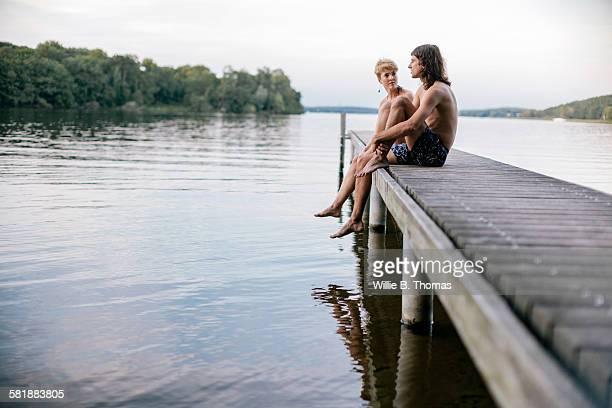 Couple sitting on wooden pier