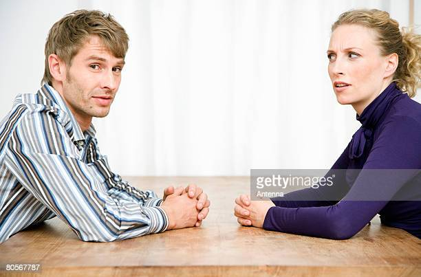 A couple sitting opposite each other at a table