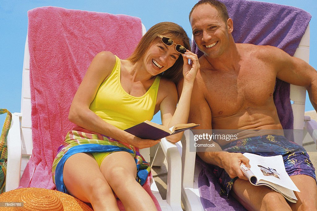 Couple sitting outdoors and reading : Stockfoto