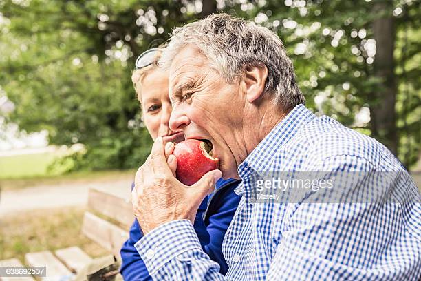 Couple sitting outdoors, mature woman sharing apple