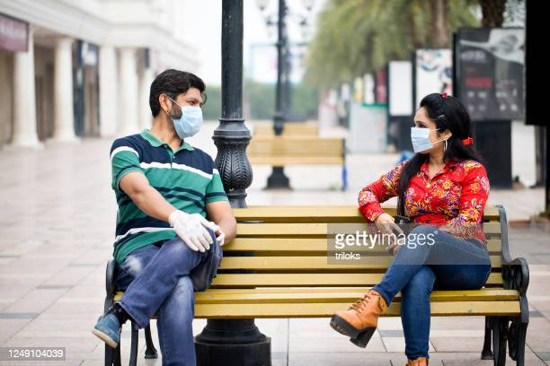 couple sitting outdoors with social distancing - social distancing stock pictures, royalty-free photos & images