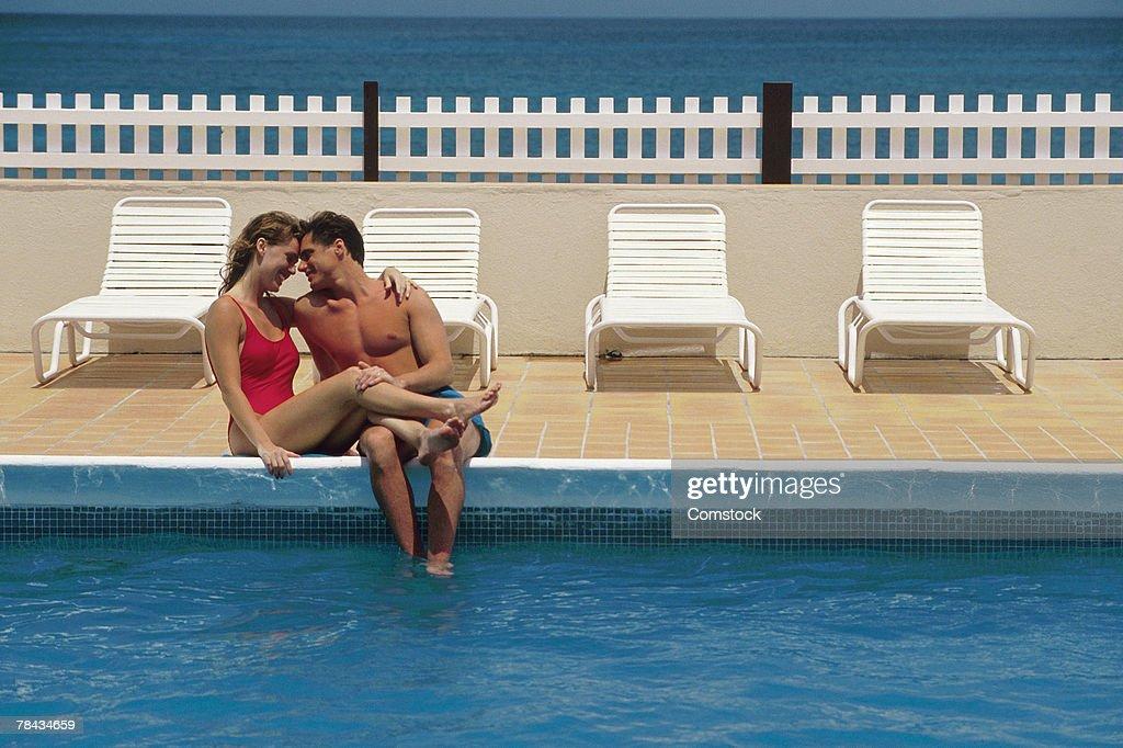 Couple sitting poolside : Stockfoto