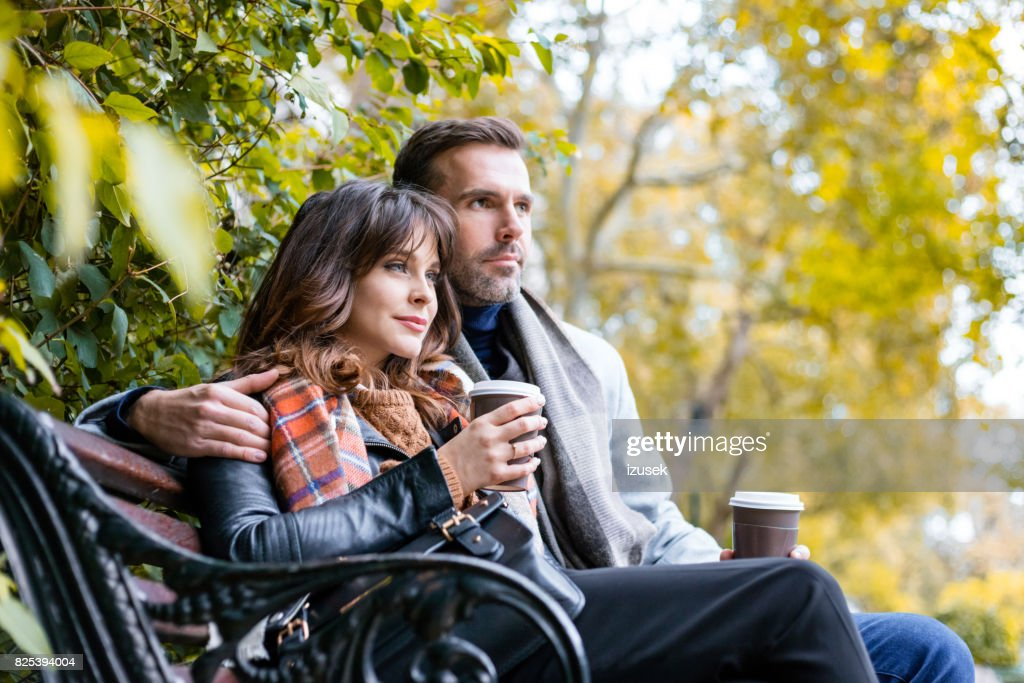 Couple sitting relaxed at park with cup of coffee : Stock Photo