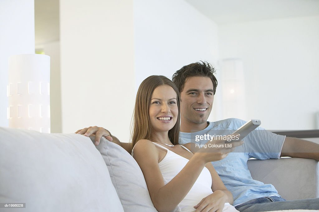 Couple Sitting Side by Side on a Sofa Watching TV and Holding a Remote Control : Stock Photo