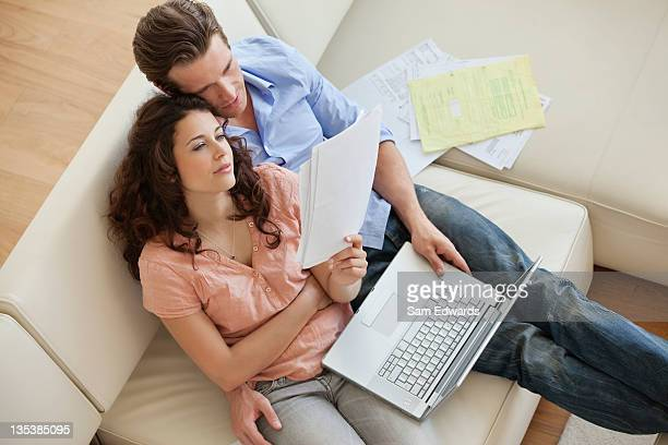 Couple sitting sofa paying bills together