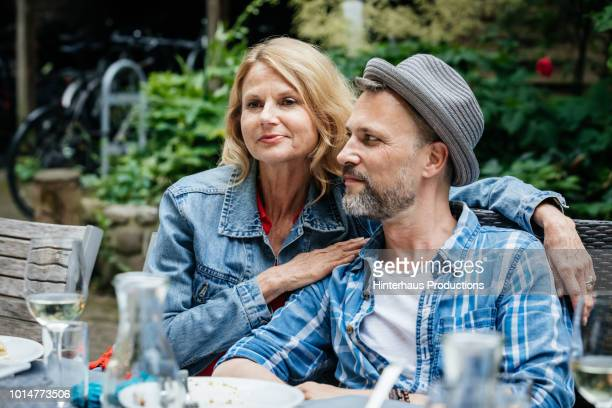 couple sitting together at family bbq - hoofddeksel stockfoto's en -beelden